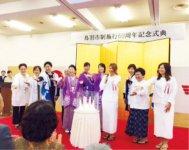 記念式典で商品をPRするメンバーと野村会長(左から5人目)