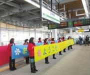 上越妙高駅に到着した「はくたか」551号を横断幕で出迎える女性会メンバー