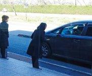 宿泊客を見送りに出る支配人とホテルスタッフ。車が見えなくなるまで外に立つ