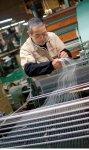 100余年の伝統技術を受け継ぐ職人たち。指先で糸を巧みにたぐり、手足の一部のように織り機を操る姿は圧巻だ