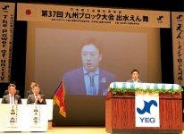 壇上で各務原市での全国大会をPRする田中暢之大会会長