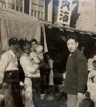 昭和30年ごろ、店の前で。二代目の祖父(右)と、生まれて間もない弘次さん(中)を抱く三代目の父