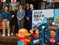 新津YEGの諸橋晋太郎会長(前列左)、当時青年部の事務局員だった近藤雄二さん(後列右)と店長の本間満さん(後列左)。手前は店舗を取材した総務広報委員会の2人(手前看板)