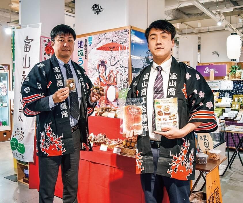 富山商工会議所の今川清司さん(左)と岸本光さん(右)が菓子や生ハムを紹介
