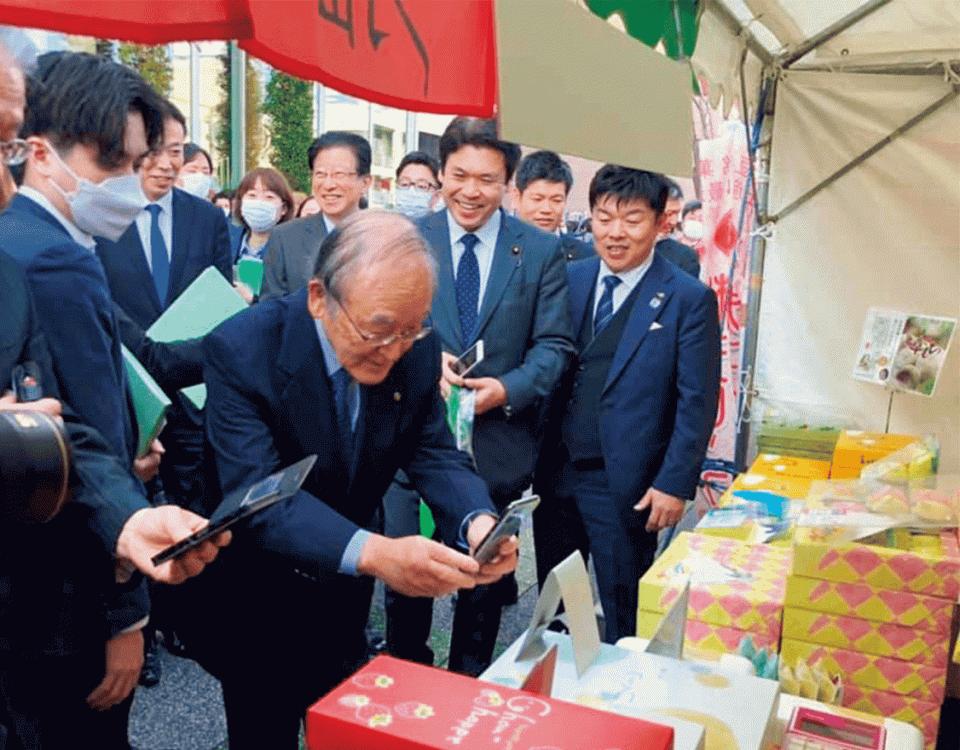 物産展でキャッシュレス決済を行う三村会頭(中央)と松本副大臣(前列右から2人目)