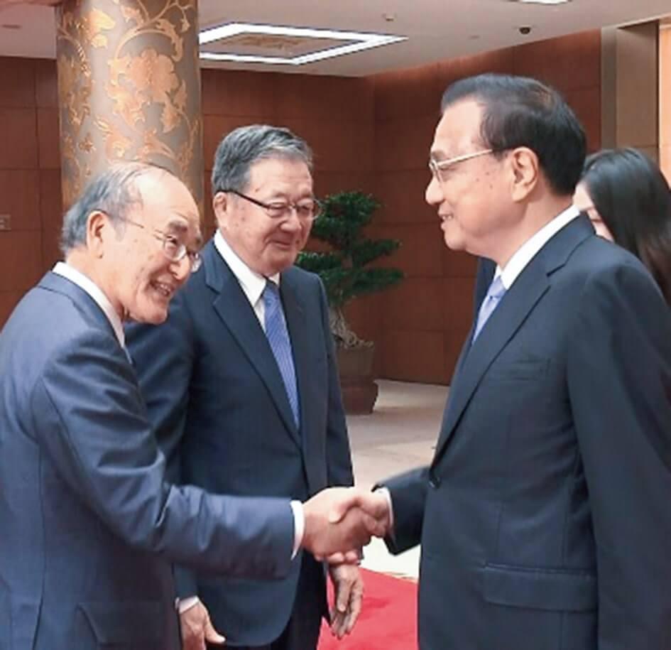 握手する李首相(右)と三村会頭