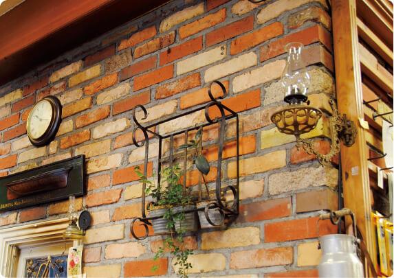 灯油で火をともすアンティーク・ランプが店内のところどころに。ランプの明かりで照らされたレンガが美しい
