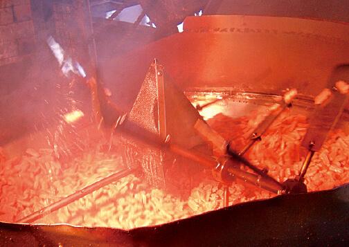 揚げ菓子は油の入った大きな窯でかき回され、香ばしい色に変わる