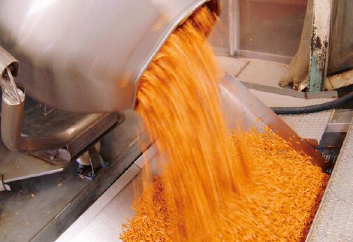 柿の種は焼き終わると黄金のレシピで配合された「味」がドラムの中の生地に噴霧される