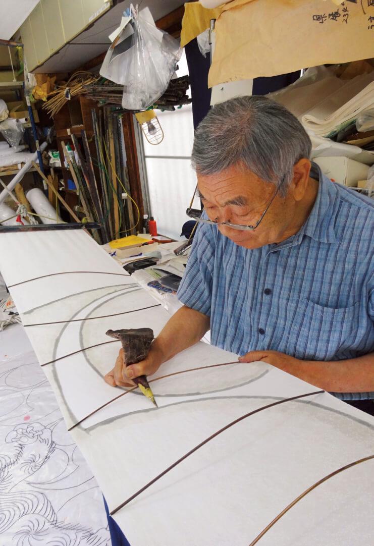 6代目、先代社長の大川原静雄さん。もち米でつくったのりを布に塗っていく「のり置き」という作業を行う様子