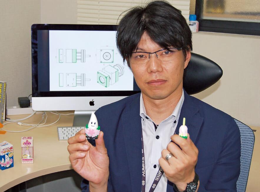 製造業ご当地お土産プロジェクトでつくった「サクラコマ」と「とことこイーナちゃん」を手に持つ橋爪良博さん