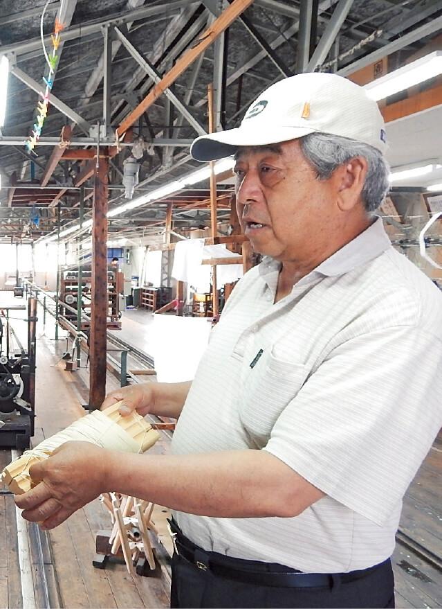 細い絹糸を丁寧に扱い、手作業で12 の工程を経てつくられる弦。「100年続く伝統の技です」と話す橋本圭祐さん