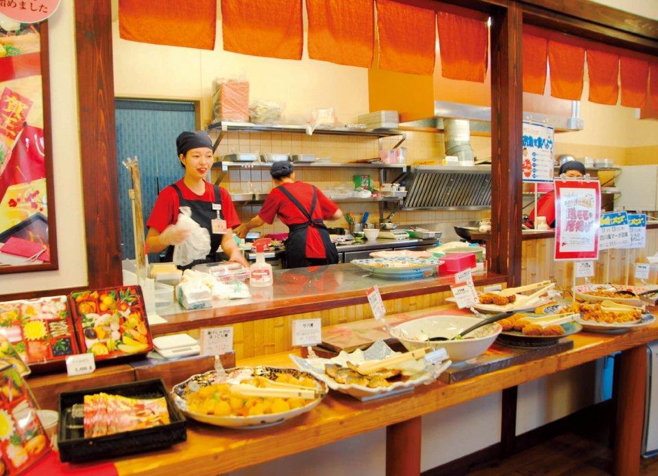 「おかずのお店クック・チャム」にはひっきりなしにお客が訪れる。接客や惣菜づくりなど、店舗を切り盛りするのは「パートナー社員」(赤いTシャツ)の女性だ
