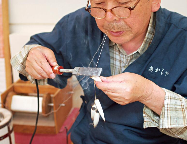麻糸でまとめられた穂首の根本部分を焼きゴテで焼いて締めると、穂首は完成する