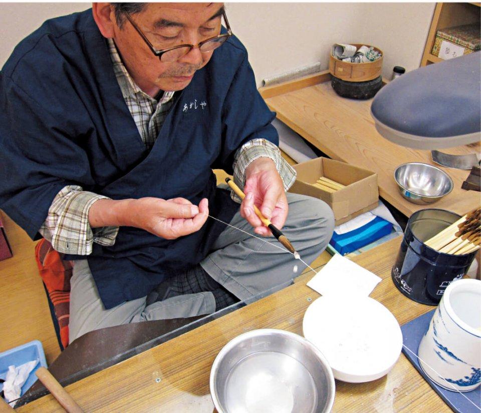 筆作りの仕上げ作業。筆軸に取り付けた穂首に布海苔(ふのり)を染み込ませ、糸を巻いて余分な布海苔を絞り出す。あかしやは分業制ではなく、一本一本の筆を一人の職人さんが完成までつくり上げている