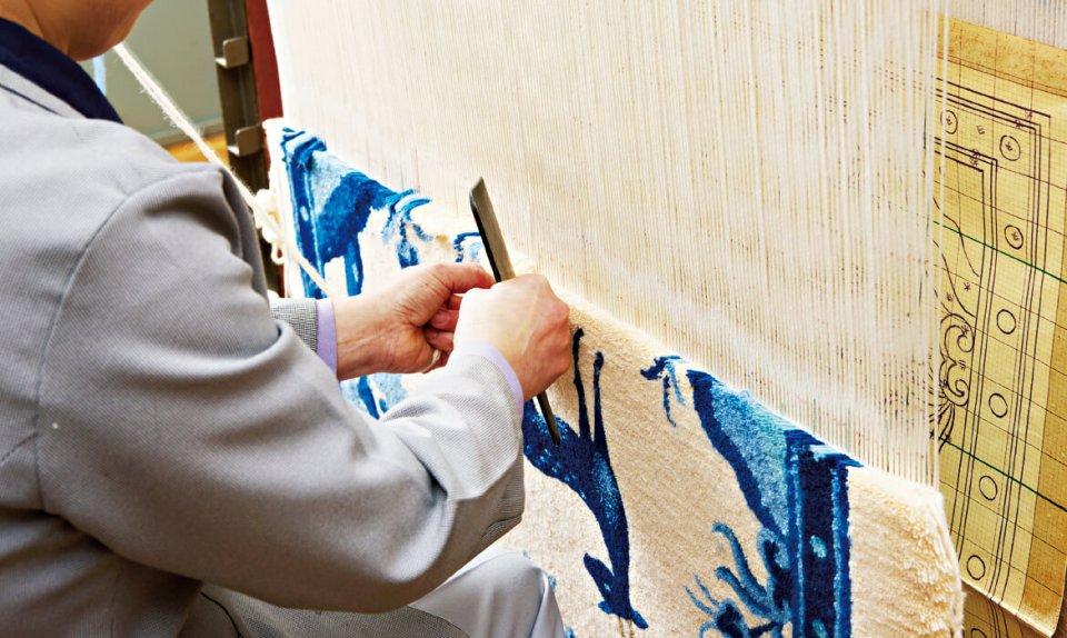 細やかな設計図をもとに縦糸に糸を結びカット。この作業を繰り返し、専用の道具で織り目の密度を一定に整える。熟練の職人でも1日に織り上げられる長さは7㎝程度