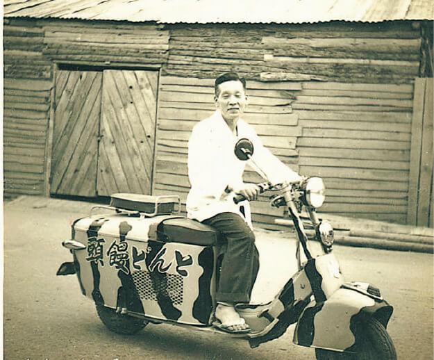 店のトレードマークである虎柄のスクーターにまたがる、14代目の高田銀一さん