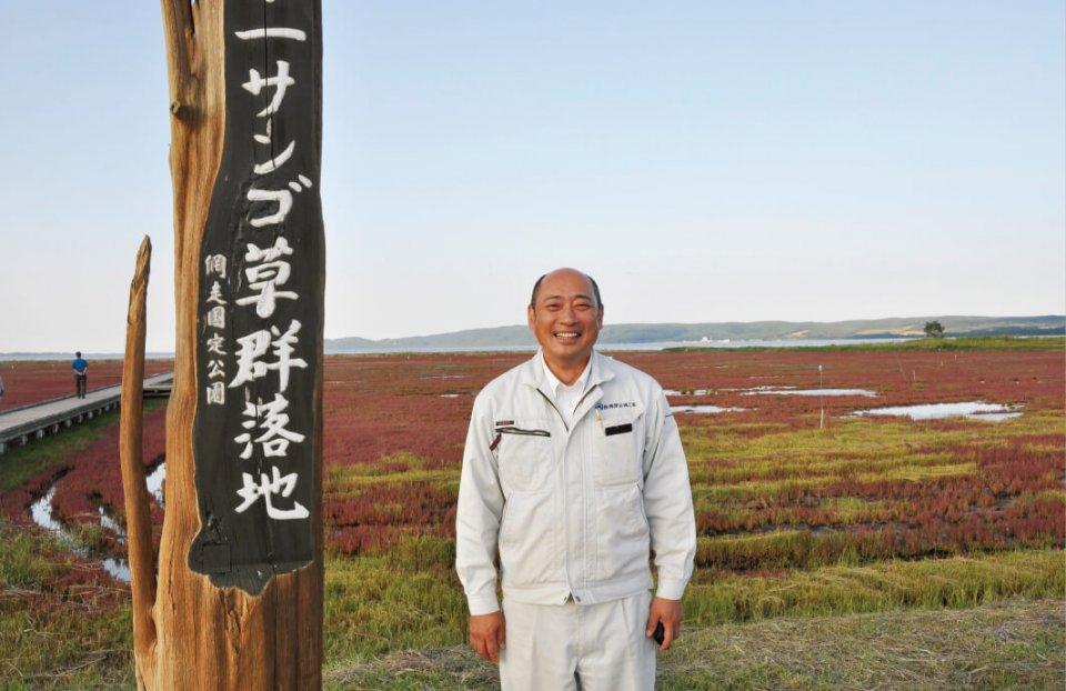 サンゴ草の群生地で笑顔を見せる飛澤隆洋さん。網走のご当地キャラ「ニポネ」の応援プロジェクトのリーダーを務める