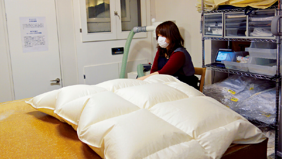 サイクロン充填機を使って、オリジナル羽毛布団を製作中の女性社員