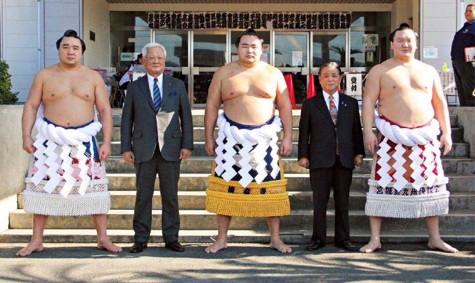 霧島市制10 周年を記念して行われた霧島場所。場所中には三横綱と西会頭(左から2 人目)、前田終止市長(同4 人目)で記念撮影もした