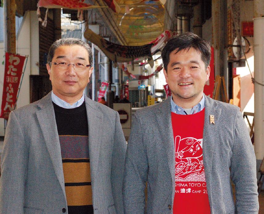 """油津商店街振興会の吉川弘範会長(左)と""""サポマネ""""の木藤亮太さん(右)。「商店街内で新陳代謝ができる仕組みを考えていく必要があると思っています」(吉川会長)。「人口が少ないまちの商店街なので、あらゆる年代の人たちに来てもらえる商店街にしていきたい」と話す木藤さん"""