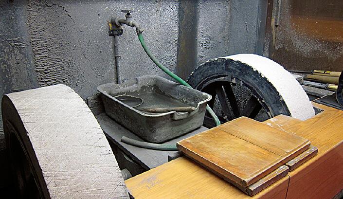 直径75センチの回転砥石で荒砥をしている。昔はこれにも天然物の砥石を使っていたという
