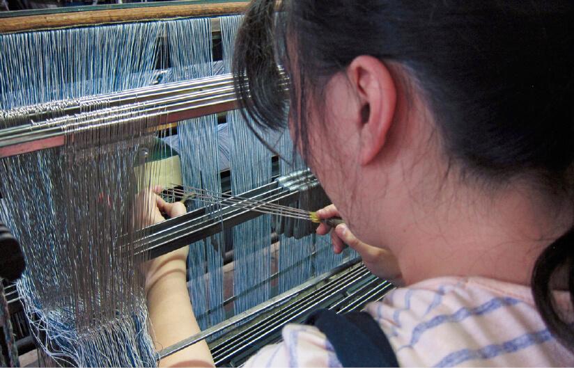デニムを織りあげていくために、タテ糸一本一本を針金の穴に通していく。3千本の糸を通し終わるのに丸1日かかる