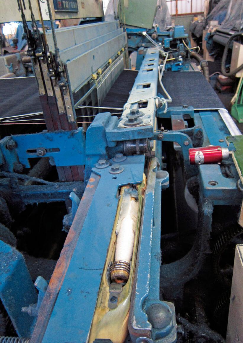 手前に見えるのが木製のシャトル。これがタテ糸の間を往復することでヨコ糸を通していく