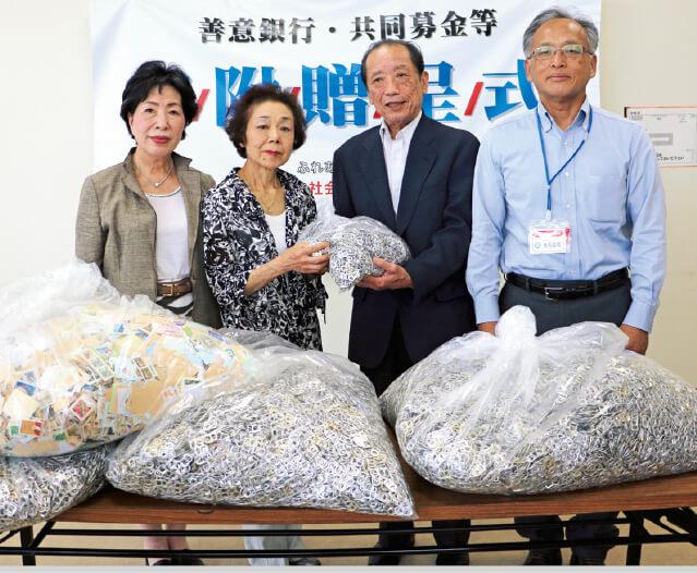 周南市社会福祉協議会にプルタブと古切手を手渡す石丸会長(左から2人目)