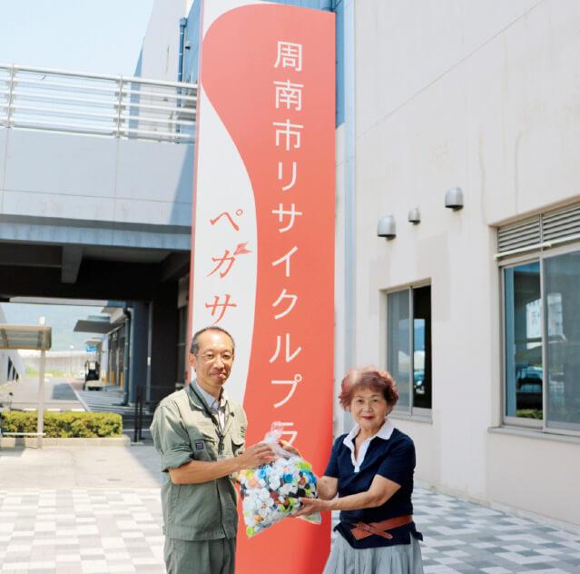 周南市環境生活部リサイクル推進課にペットボトルのキャップを手渡す矢頭雅子副会長(右)