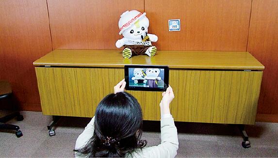 同所が提供するさのまるピクチャ。佐野市内の店舗でスマートフォン用アプリを起動し、スマートフォンのカメラをフォトマーカーに向けると画面上にさのまるが現れ記念撮影ができる