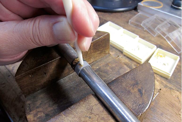 鹿の角でできた道具で金属に金箔を打ち込んでいく
