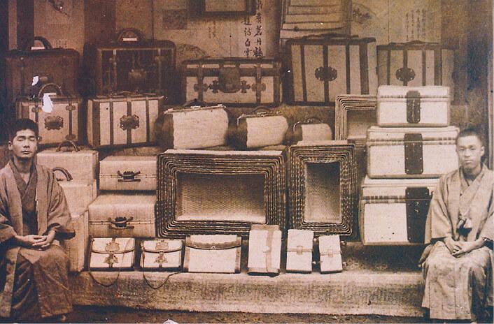 柳行李・行李鞄:1900年「パリ万国博覧会」で銀賞を受賞した際の写真。入れ子状の柳行李や三本革締め行李鞄が見える