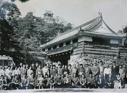昭和36年に社員旅行で高知城に行った際の記念写真。50人以上の社員が写っている