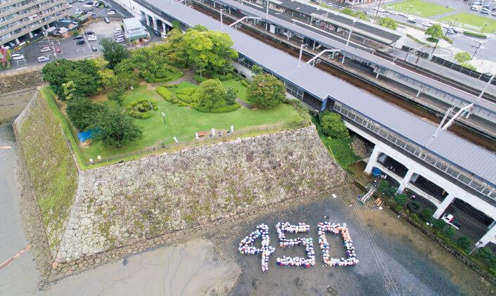 この先100年続く風景を残そうと広島経済同友会三原支部は、市民ボランティアとかいぼりを実施し人文字を作って記念撮影