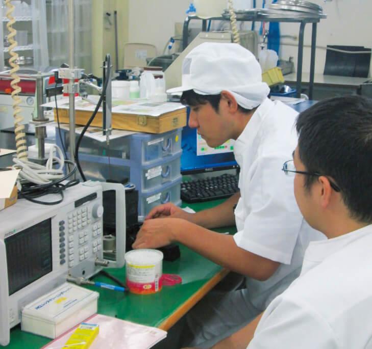 製造業での実習。職員に説明を受けながら、実際に機械を使って業務を行う