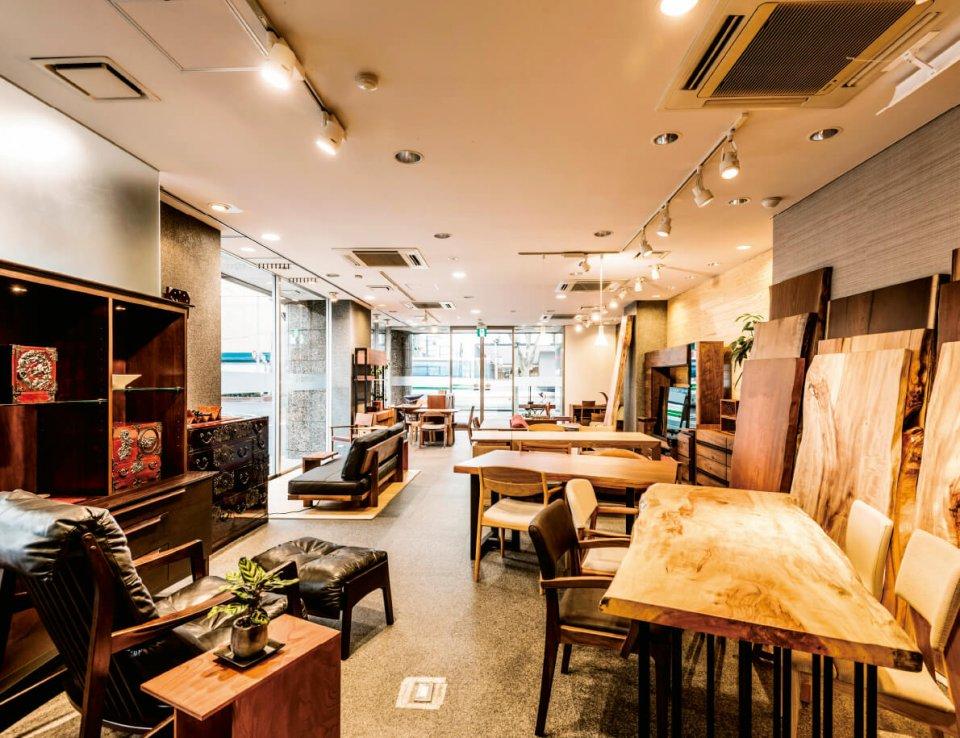 monmaya大町店の店内には、テーブル用の無垢材や家具とともに、仙台たんすやmonmaya+の製品などが展示されている