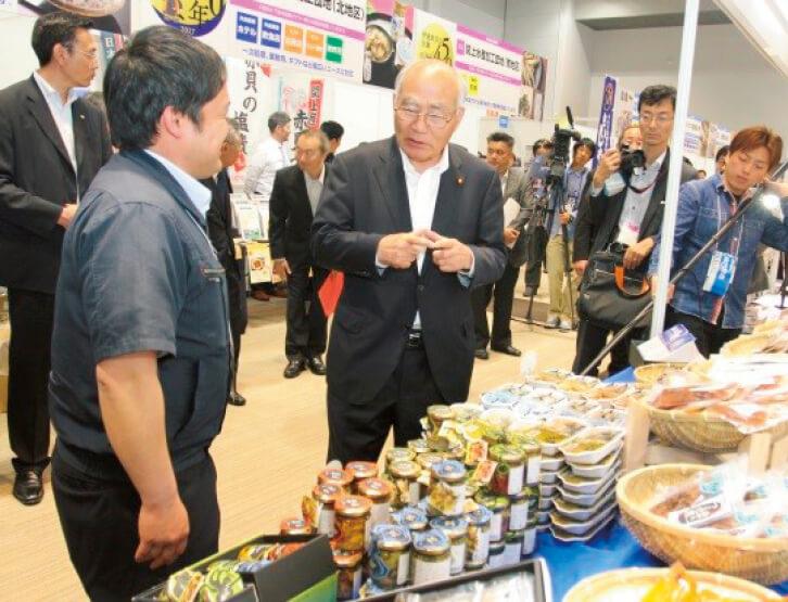 共催事業の東北復興水産加工品展示商談会2017を吉野正芳復興大臣が視察。バイヤー担当者と出展者との交流も積極的に行われた
