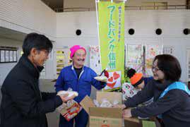 寄贈された食品を受け取る沓掛会長(右)(写真:東信ジャーナル社提供)