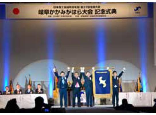 岐阜かかみがはら大会で次会長へ大会旗の引き継ぎの一幕
