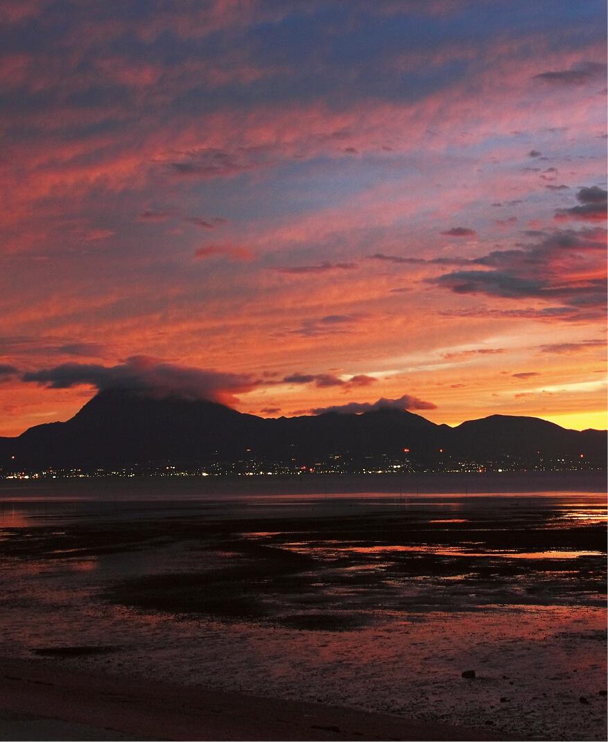 有明海:夕日を背景に遠浅な有明海越しに望む雲仙普賢岳