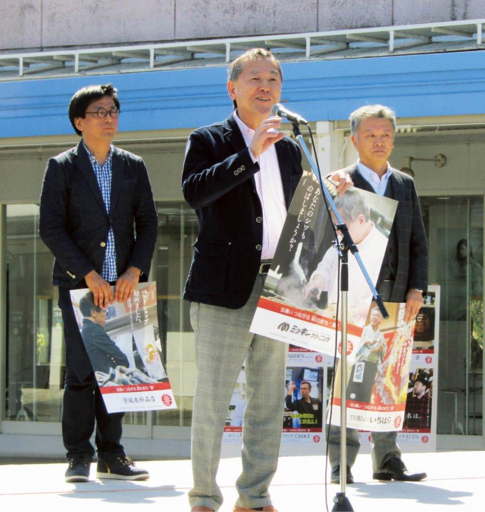 3月10日、ポスターを披露し、あいさつする松下優副会頭(中央)、市原義彦副会頭(右)ら