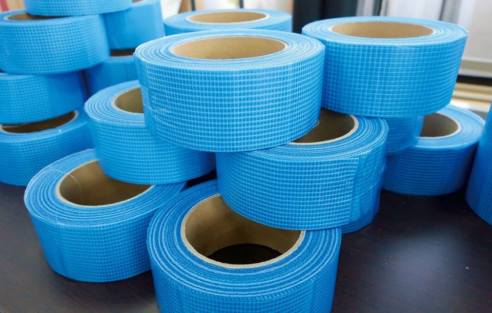 新製品の粘着剤付き薄葉紗細幅テープは、薄い寒冷紗と薄いフィルムを貼り合わせている。建築資材や壁ひび割れ補強材として使われる