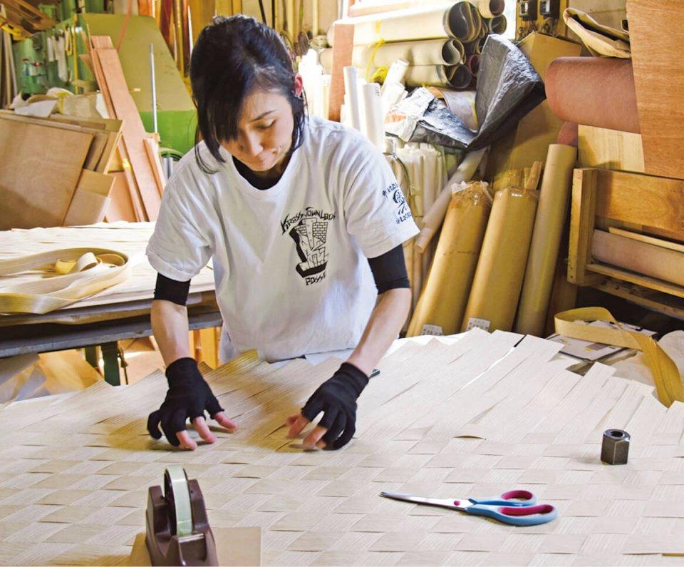 厚さ0.5mmほどのツキ板を網代に編んでいるところ。この工程は全て手作業だ