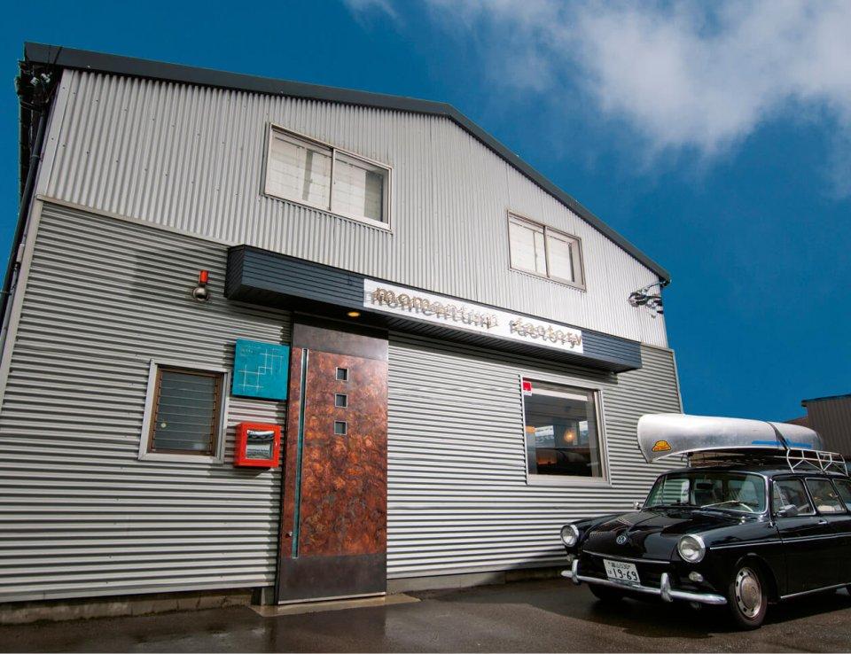 本社兼工房は、代表色の斑紋孔雀色の玄関ドアや、人気の斑紋ガス青銅色の表札がアクセントのモダンな佇まい
