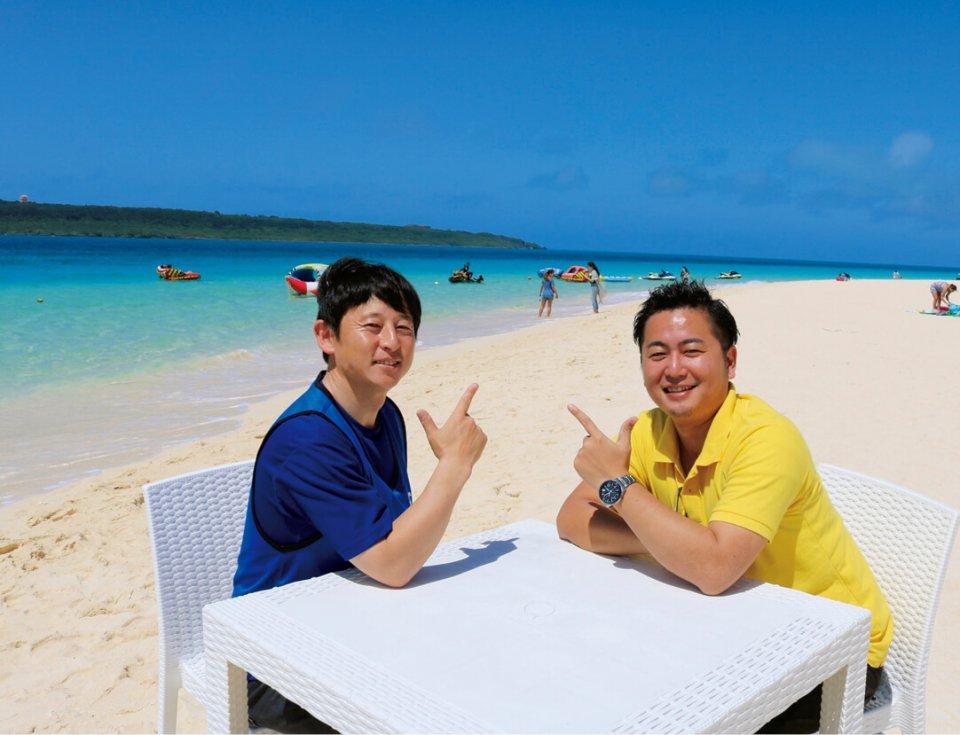 宮古島の輝いている海とまぶしい日差しの中でインタビューをしている野村氏(左)と坂口氏