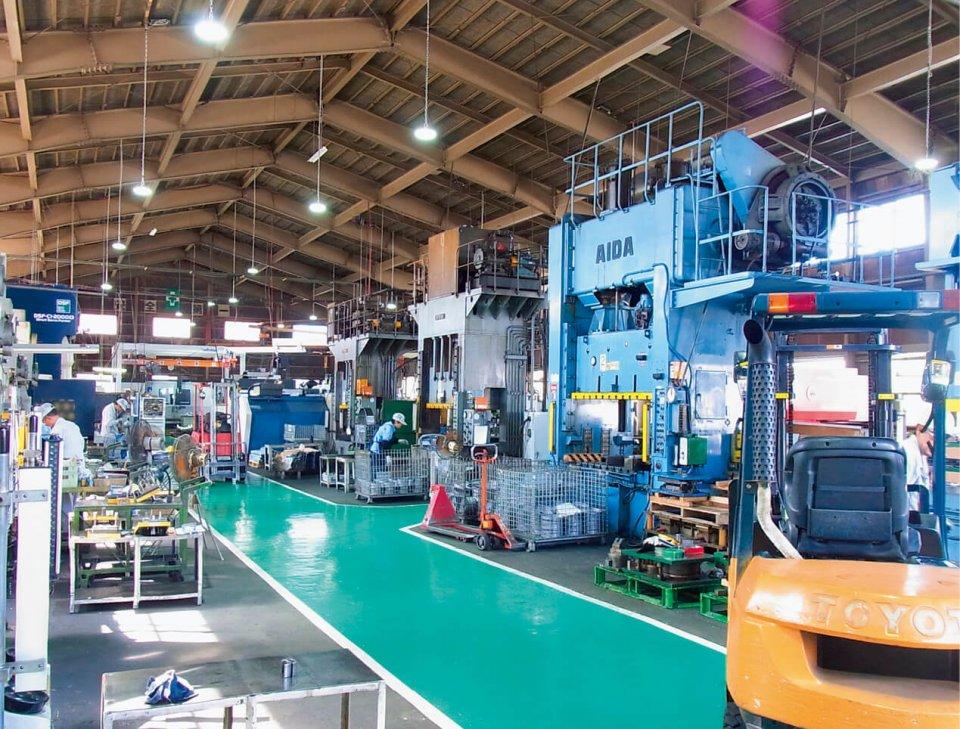 各種プレス機が並ぶ工場内。中央に広めの通路幅を確保し、床を色分けして安全性と作業効率を高めている