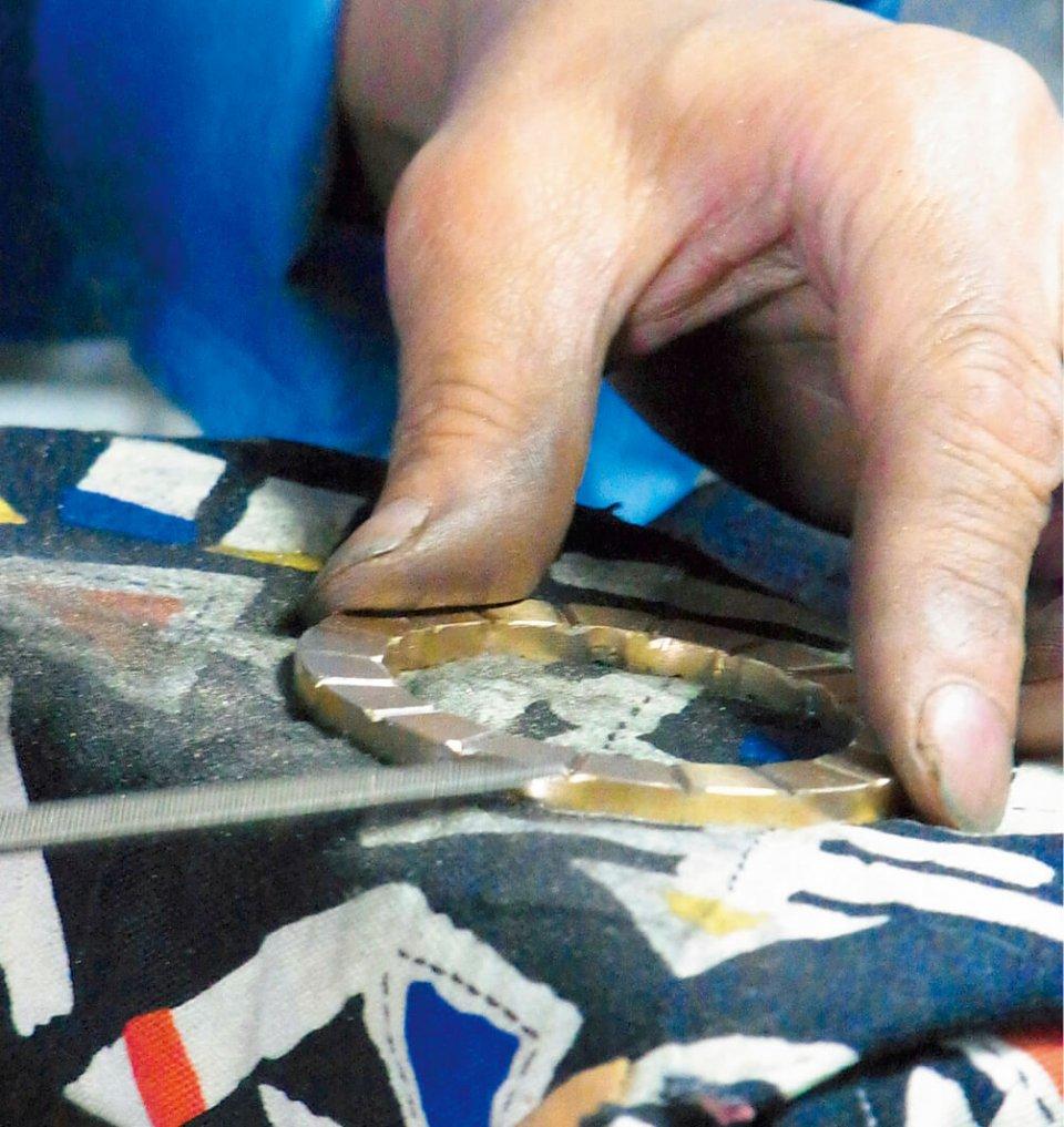 スラスト軸受の凹部のエッジを研磨している女性は20年のキャリアを誇る。絵画は賞を取るほどの腕前で、手先の器用さ、仕上がりの美しさに定評がある
