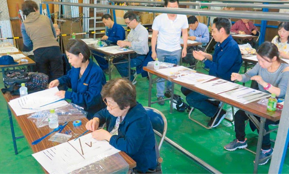 鋼製建具や装飾金物製品製造のマエダでモビールの組み立てを体験するバスツアー参加者