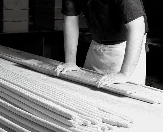 のし板(より板)で棒状に固める作業は、職人の長年の経験が光る技の一つ